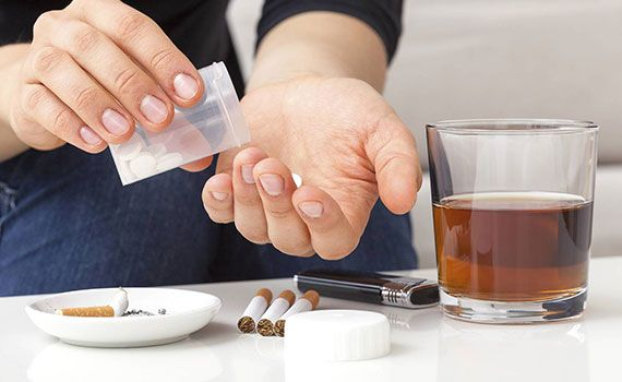 Hands taking pills next to a drink and cigarettes for Alpha Center Drug & Alcohol Treatment