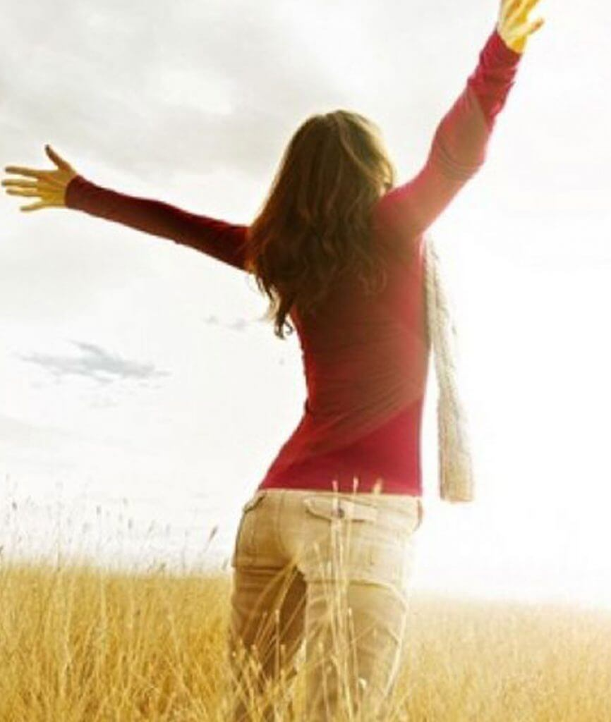 Woman in field with arms triumphantly in the air after counseling at Alpha Center Psychological Services
